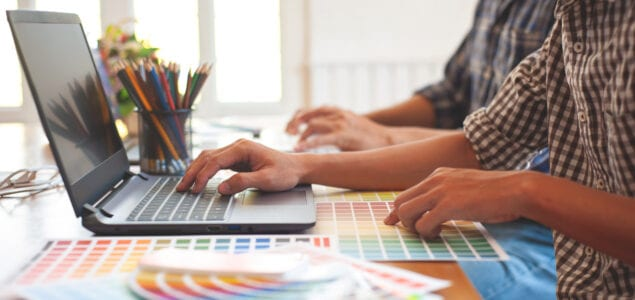 two people using color charts to design graphics on computer