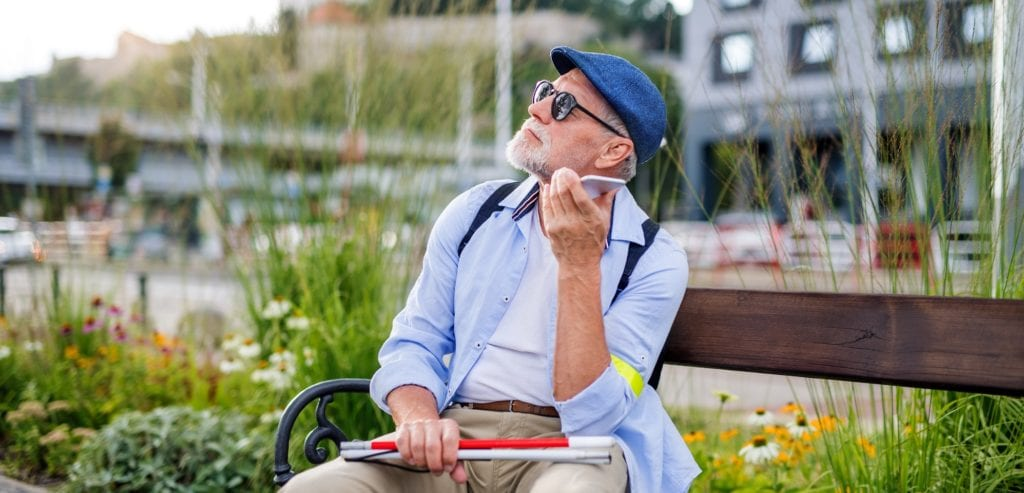 blind man holding a folded cane, sitting on a park bench in an urban environment and listening to his phone