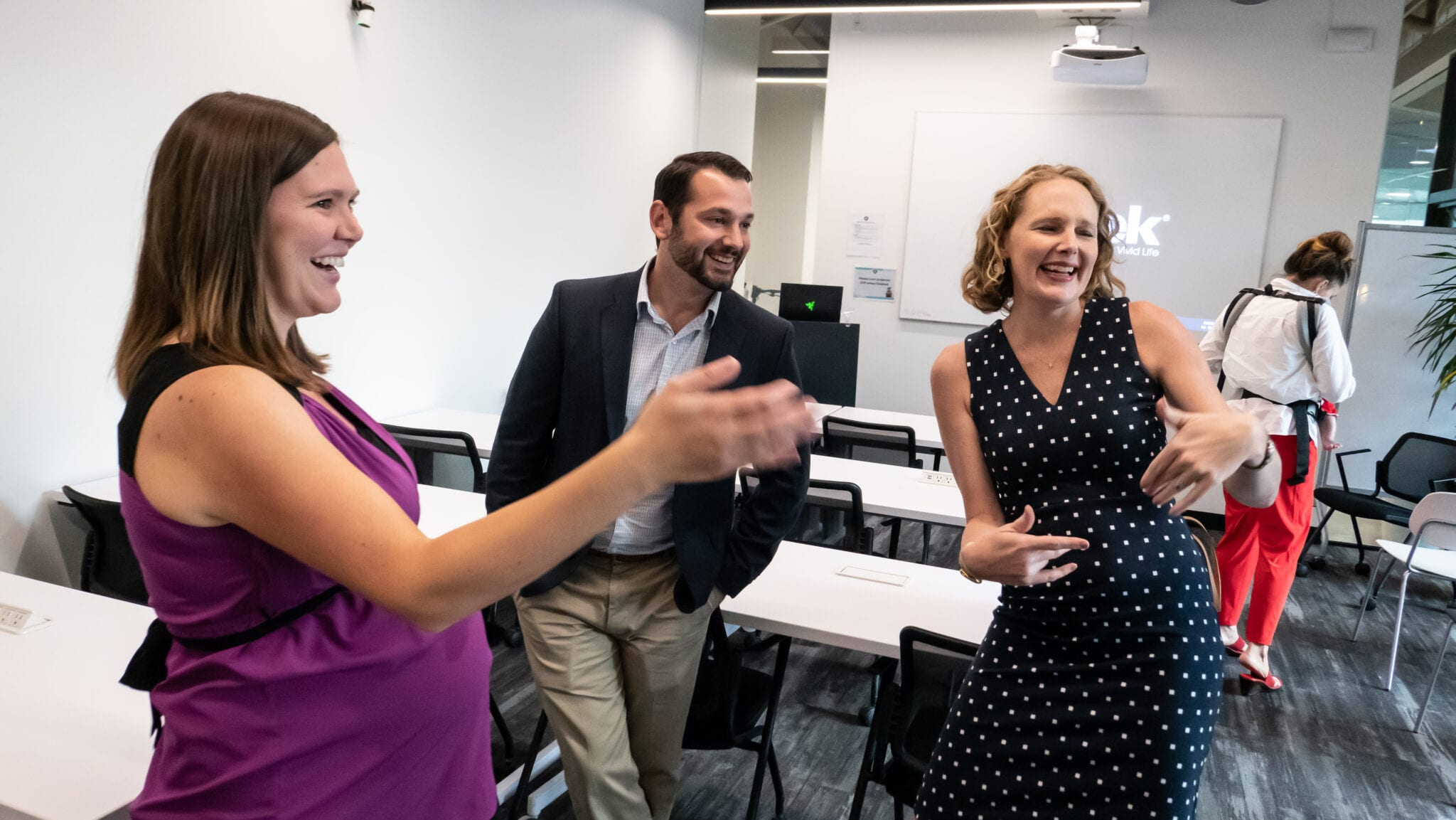 Amber and a man and woman at a meetup event laughing