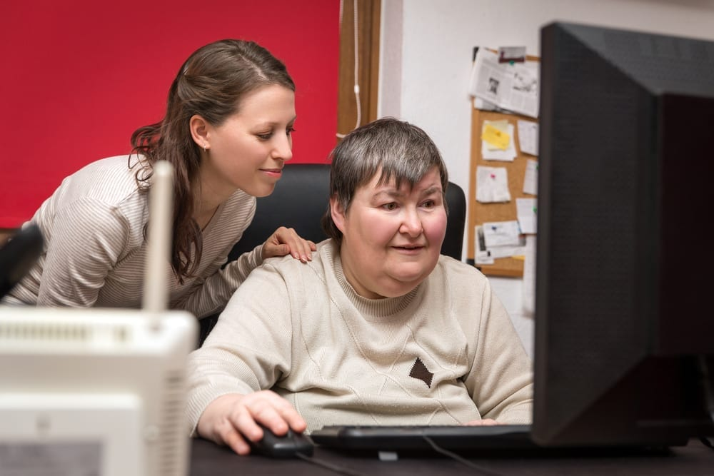 Disabled woman and caregiver looking at computer